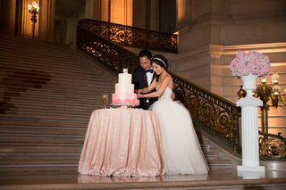 bride-in-a-strapless-kenneth-pool-dress-with-tulle-skirt-groom-in-black-tux-cut-a-pink-white-cake
