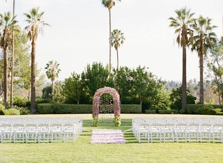 white-chairs-and-pink-floral-arch-on-lawn-surrounded-by-palm-trees
