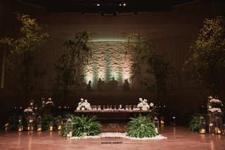 dark-wedding-ceremony-church-with-trees-brought-into-church-wedding