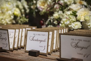 outdoor-ranch-wedding-reception-with-place-cards-with-burlap-print-edges-propped-on-tiny-wood-blocks