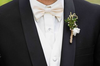 groom-wearing-white-bow-tie-and-boutonniere-in-twine