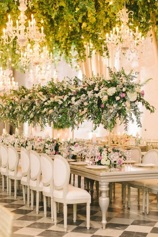 wedding-reception-checkerboard-floor-white-chairs-tables-tall-centerpiece-greenery-chandelier