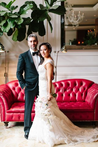 bride-in-maggie-sottero-wedding-dress-cascading-bouquet-with-groom-in-tuxedo-bow-tie-red-chaise