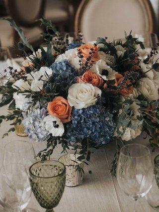 wedding-reception-low-centerpiece-blue-hydrangea-white-anemone-peach-rose-greenery-thistle-lavender