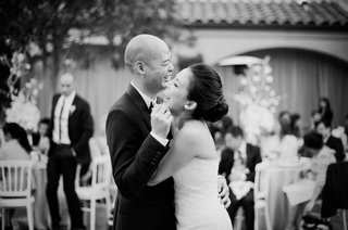 black-and-white-photo-of-bride-and-groom-laughing-during-first-dance