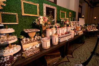 dessert-table-in-front-of-wall-of-greenery-with-empty-frames