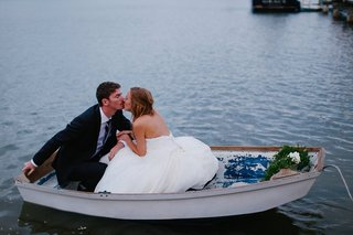 groom-in-black-suit-kisses-bride-in-a-strapless-martina-liana-dress-as-they-sit-in-a-white-rowboat
