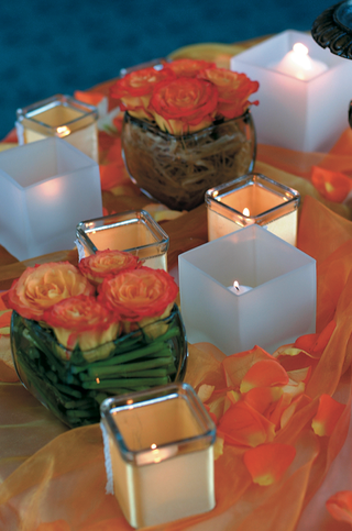 orange-flowers-in-vases-and-votive-candles