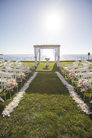 grass-lawn-oceanfront-outdoor-ceremony-with-white-drapery-and-flower-chuppah-and-flower-petals-aisle