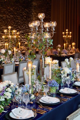 wedding-reception-high-gloss-table-gold-flatware-blue-purple-flower-centerpiece-candles-taper