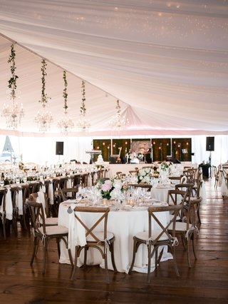 wedding-reception-wood-flooring-white-tent-chandeliers-x-back-wood-chairs-white-linens-flowers