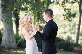bride-in-strapless-wedding-dress-holds-grooms-hands-in-forest-strapless-gown-loose-updo-hairstyle