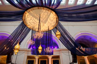 hanging-lighting-concept-and-chandeliers-with-sheer-dark-blue-fabric-and-purple-uplighting