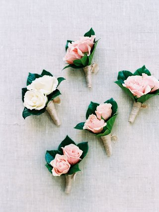 groom-white-two-flower-boutonniere-and-groomsmen-pink-boutonnieres-two-flowers-roses