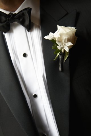 groom-wearing-tuxedo-fastened-with-rose-and-stephanotis