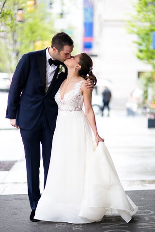 lace-v-neck-wedding-dress-a-line-gown-from-kleinfeld-bridal-by-rivini-kissing-groom-holding-train