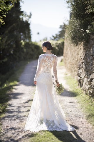 back-view-of-bride-standing-on-dirt-road-in-inbal-dror-lace-wrap-wedding-dress