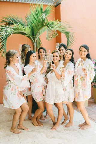 wedding-party-bridesmaids-in-pale-peach-flower-print-robes-bride-in-white-lace-robe-romper-champagne