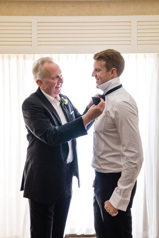 father-of-the-groom-in-suit-helping-son-get-ready-put-on-bow-tie-in-grooms-suite