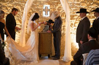 bride-and-groom-at-altar-with-cross-doing-sand-ceremony-tradition