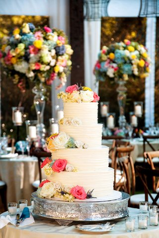 white-wedding-cake-four-layer-with-fresh-flowers-on-top-of-each-layer-tier-pink-blue-yellow-white