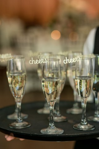 laser-cut-gold-cheers-embellishment-attached-to-champagne-glasses