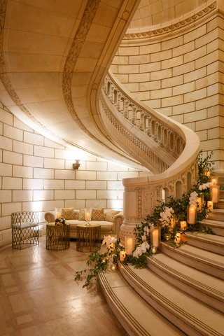 wedding-reception-grand-staircase-decorated-with-greenery-candles-white-flowers-chesterfield-sofa
