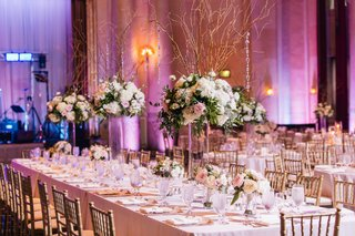 long-dinner-table-with-tall-centerpieces-with-branches-and-flowers-and-smaller-flower-arrangements