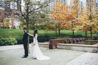 bride-in-lace-long-sleeve-wedding-dress-taps-grooms-shoulder-in-chicago-park