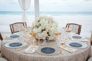 ocean-view-tent-wedding-reception-table-sequins-low-centerpiece-gold-rim-glasses-wood-chairs-island