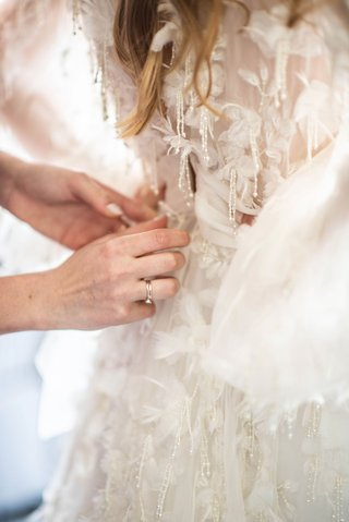 bride-in-marchesa-wedding-dress-beads-appliques-designer-being-put-on-by-mother