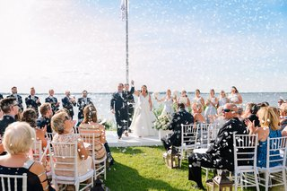 wedding-ceremony-near-water-waterfront-wedding-grass-lawn-white-chair-lanterns-confetti-happy-guests