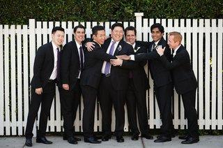 groom-and-groomsmen-smile-and-hug-before-wedding-ceremony-purple-ties-light-purple-dark-purple