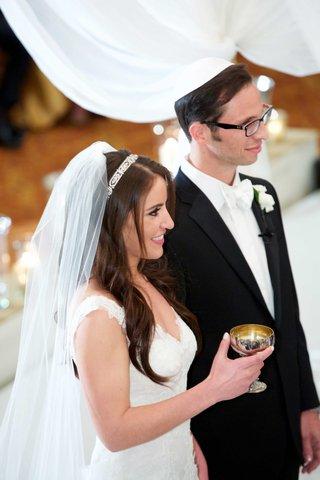 jewish-wedding-ceremony-bride-in-monique-lhuillier-wedding-dress-headband-holding-kiddush-cup