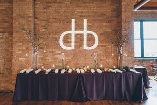 modern-wedding-monogram-on-brick-wall-over-table-decorated-with-flowers-branches-and-escort-cardsq