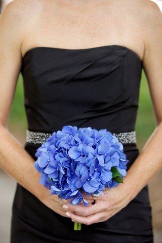 bridesmaid-in-black-dress-holding-blue-hydrangeas