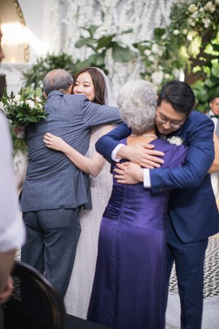 bride-hugging-father-and-groom-hugging-mother-at-ceremony