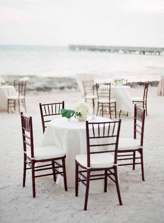 beach-wedding-cocktail-hour-on-sand-in-key-west-with-wood-chairs-white-tablecloth-linens