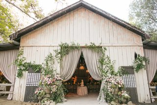 white-wash-wood-barn-with-drapery-greenery-wood-boards-with-escort-cards-for-reception