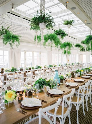 wedding-reception-long-table-wood-with-white-chairs-ferns-from-ceiling-low-arrangements-of-flowers