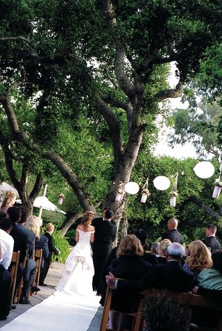 bride-and-groom-at-altar-beneath-tree-and-paper-lanterns