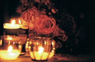 rose-arrangements-next-to-floating-candles-at-wedding
