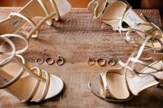 brides-shoes-lay-next-to-wedding-and-engagement-rings