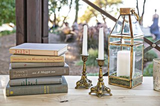 wedding-reception-decor-vintage-inspired-old-books-with-gold-candlesticks-lantern-candles