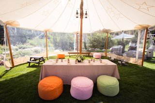 outdoor-tent-with-clear-windows-and-colorful-ottomans