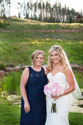 bride-in-strapless-watters-wedding-dress-with-mother-of-bride-in-pearls-and-blue-dress