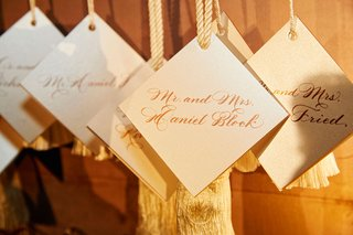 wedding-reception-escort-card-display-on-wall-calligraphy-white-tassel-diamond-shape