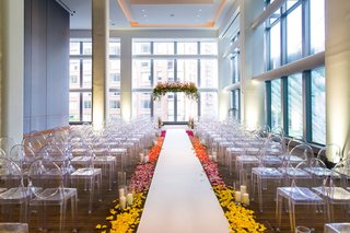 wedding-with-ghost-chairs-ceremony-lucite-acrylic-chairs-and-ceremony-arch-flowers-bright-colors