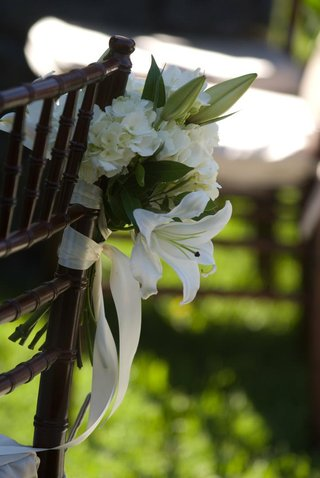 white-flower-arrangement-tied-to-ceremony-chair