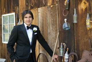 groom-in-tuxedo-next-to-cabin-with-horse-shoes